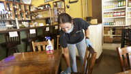 Carlee Packard wipes down a table and chairs after customers finished eating at Puckett's Grocery & Restaurant.