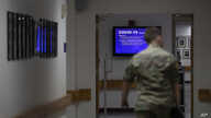 FILE - In this March 25, 2020, file photo a member of the U.S. Army walks down the hall toward a monitor displaying COVID-19…