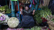 A vegetable vendor prays as medical workers from the Ministry of Health seek volunteers for new coronavirus tests at La…