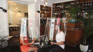 A man and a woman demonstrate dining under a plastic shield Wednesday, May 27, 2020 in a restaurant of Paris. As restaurants in…