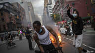 Protesters march down the street as trash burns in the background during a solidarity rally for George Floyd, May 30.