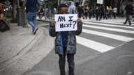 A boy holds a sign during a protest in downtown Los Angeles, California, May 29, 2020, over the death of George Floyd, who died in police custody on Memorial Day in Minneapolis.