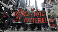 People hold signs as they march during a protest over the death of George Floyd, in Chicago, Illinois, May 30, 2020.