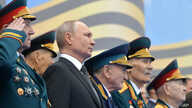 FILE - Flanked by World War II veterans, Russian President Vladimir Putin watches a military parade marking 74 years since the end of World War II, in Red Square, in Moscow, Russia, May 9, 2019.