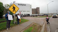 FILE - Residents hold 'thank you' signs to greet employees of a Smithfield pork processing plant in Sioux Falls, South Dakota, May 20, 2020, as they resume working after the plant's three-week closure because of a coronavirus outbreak.