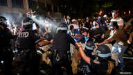 A police officer sprays protesters in the Brooklyn borough of New York City during a march against the death of George Floyd in Minneapolis police custody, May 30, 2020.