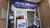 A customer walks out of a U.S. Post Office branch and under a banner advertising a job opening