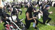 Anjel Newmann, 32, kneels while scanning her phone during a peaceful rally in Providence, R.I. on June 5.