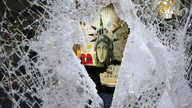A Statue of Liberty painting is seen through a smashed Dolce and Gabbana store window, Monday, June 1, 2020, in the SoHo…