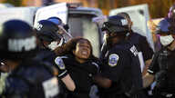 With tears in her eyes, a demonstrator is taken into custody by police after a curfew took effect during a protest