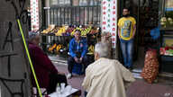 Men sit outside a grocery shop in Athens, June 5, 2020. The European Commission says Greece is likely to suffer deepest recession in the eurozone this year, but first quarter growth figures were better than expected.