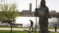 FILE - A man walks past a statue of Sacajawea along the banks of the Missouri River in Great Falls, Montana.