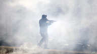 A police officer moves through tear gas deployed to disperse protesters in Philadelphia, Pennsylvania, May 31, 2020.