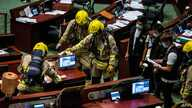 Members of the fire brigade conduct decontamination work in the main chamber of the Legislative Council after pan-democrat…