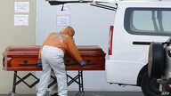 Employees of a funeral parlour put the coffin containing the body of a person who died of COVID-19 in the vehicle of a relative…