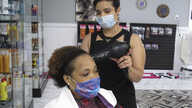 Shannon Stafford styles the hair of Ebony Housey at her salon on Friday, April 24, 2020, in Savannah, Ga. Gov. Brian Kemp…