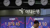 A currency trader talks on the phone near the screens showing the Korea Composite Stock Price Index (KOSPI), left, and the…