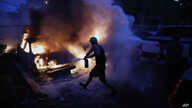 People attempt to extinguish cars on fire, Friday, May 29, 2020, in Minneapolis. Protests continued following the death of…