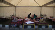 Migrant workers rest inside a tent before traveling in a Shramik train arranged to transport them to their home states, at a…