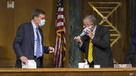 Senate Intelligence Committee Chairman Sen. Richard Burr, R-N.C. right, adjusts his mask while talking to Vice Chairman Sen…