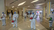 Cleaners in hazmat suits demonstrate disinfection as workers remodel a display window at Siam Paragon, an upmarket shopping…