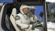 NASA astronauts Douglas Hurley, left, and Robert Behnken, wearing SpaceX spacesuits, depart the Neil A. Armstrong Operations…