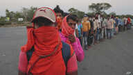 Migrant workers stand to receive food packets distributed by the postal department, on their journey to return to their home…