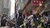 "Protesters gesture with five fingers, signifying the ""Five demands - not one less"" as they march along a downtown street during…"