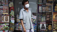 A man wearing a face mask to help curb the spread of the new coronavirus stands in front of a book store in Bangkok, Thailand,…
