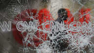 A security guard walks behind shattered glass at the CNN building at the CNN Center in the aftermath of a demonstration against…