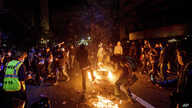Demonstrators burn garbage in Oakland, Calif., on Friday, May 29, 2020, while protesting the Monday death of George Floyd, a…