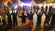 Demonstrators kneel before police Saturday, May 30, 2020, in Minneapolis. Protests continued following the death of George…