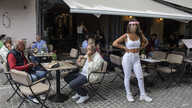A cafe-restaurant staff stands outside as people drink coffee in Monastiraki district of Athens, on Monday, May 25, 2020. …
