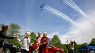 The Ferry family, from Chantilly, Va., who were in the middle of taking a family photograph, are surprised by a second fly over…