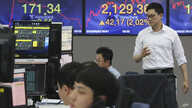 A currency trader passes by screens showing the Korea Composite Stock Price Index, right, and the foreign exchange rate at the…