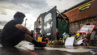 After a new mural, center, of George Floyd is added to a growing memorial of tributes, Trevor Rodriquez sits alone at the spot…