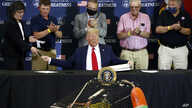President Donald Trump hands pens out after signing an executive order on commercial fishing after speaking at a roundtable…