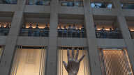 "A protester gestures with five fingers, signifying the ""Five demands - not one less"" in a shopping mall during a protest…"