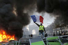 A demonstrator waves the French flag onto a burning barricade on the Champs-Elysees avenue with the Arc de Triomphe in background, during a demonstration against the rising of the fuel taxes, Saturday, Nov. 24, 2018 in Paris.