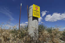 FILE - In this July 11, 2016 file photo, a sign warns of radioactive material stored underground on the Hanford Nuclear Reservation near Richland, Washington.