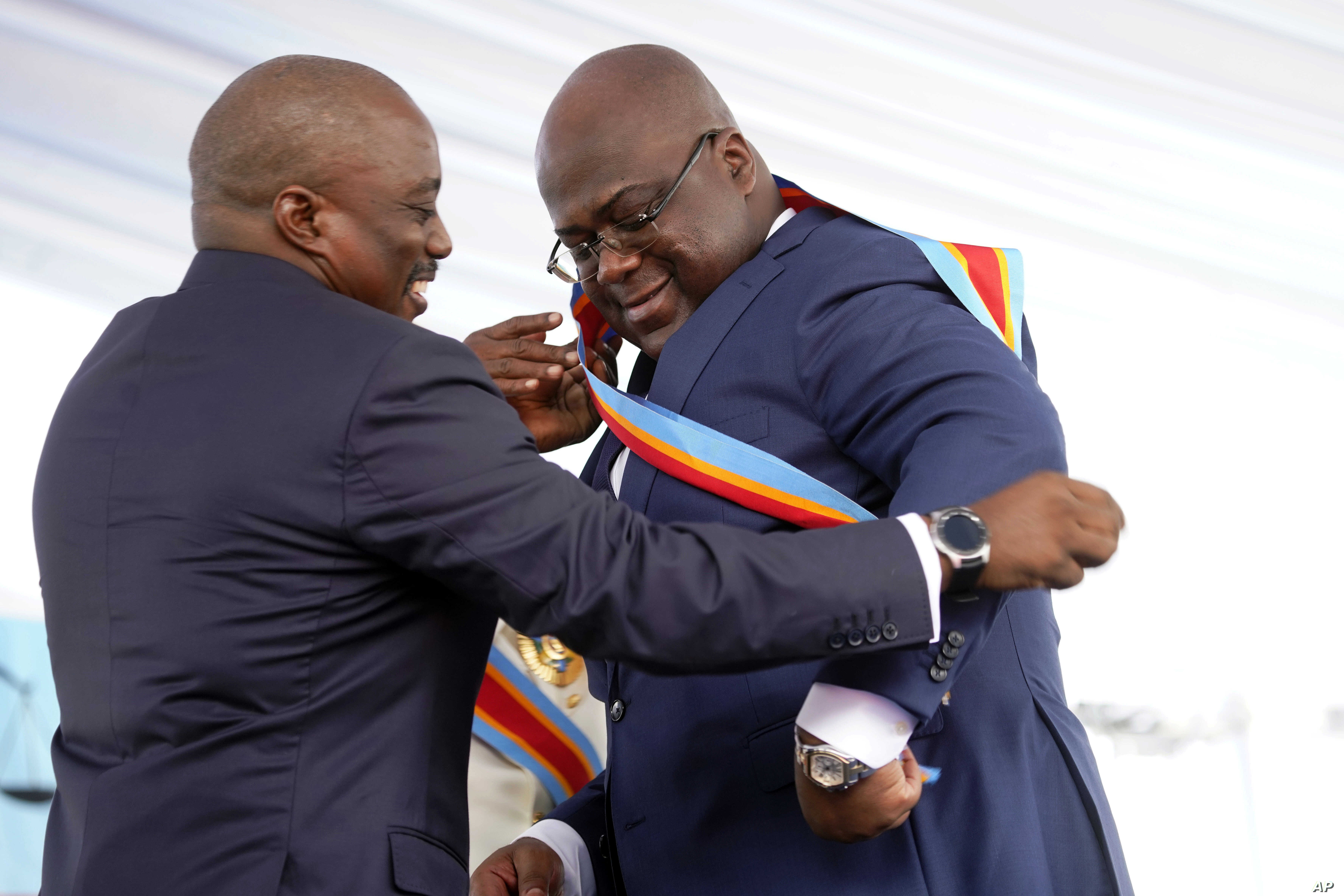 Congolese President Felix Tshisekedi, right, receives the presidential sash from outgoing president Joseph Kabila after being sworn in in Kinshasa, Democratic Republic of the Congo, Thursday Jan. 24, 2019.