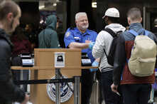 A Transportation Security Administration worker hands an identification card back to a traveler, Jan. 25, 2019, at Seattle-Tacoma International Airport in Seattle. President Donald Trump and congressional leaders on Friday reached a short-term deal t