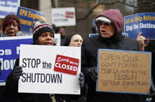 People rally to call for an end to the partial government shutdown in Detroit, Thursday, Jan. 10, 2019.