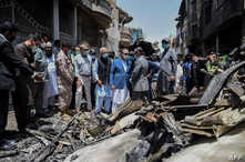 In this picture taken on May 23, 2020, and released by Pakistan's Civil Aviation Authority (PCAA), Pakistani officials inspect the site a day after a Pakistan International Airlines passenger plane crashed in a residential area in Karachi.