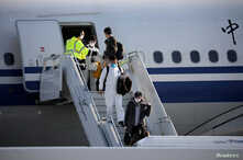 Members of an aid expedition in protective masks disembark from Air China plane carrying medical supplies donated by the…