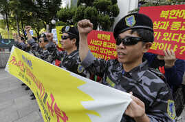 North Korean defectors shout slogans during a press conference demanding the improvement of North Korean's human rights, in front of National Human Rights Commission of Korea in Seoul, South Korea, Wednesday, Oct. 8, 2014.