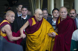 The Dalai Lama, in yellow robe, is helped by attending monks as he leaves after a religious talk at the Tsuglakhang temple in Dharmsala, India, March 14, 2017.