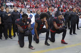 San Francisco 49ers outside linebacker Eli Harold (58), quarterback Colin Kaepernick (7) and safety Eric Reid (35) kneel during the national anthem before an NFL football game Oct. 6, 2016.