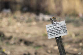 """A marker with the epitaph: """"They died for Putin's lies"""" is seen at a mass grave in the village of Nyzhnya Krynka, eastern Ukraine, Sept. 23, 2014."""