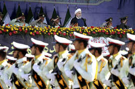Iran's President Hassan Rouhani, top center, reviews army troops marching during the 38th anniversary of Iraq's 1980 invasion of Iran, in front of the shrine of the late revolutionary founder, Ayatollah Khomeini, outside Tehran, Iran, Sept. 22, 2018....
